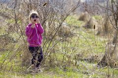 Portrait of cute small confused blond girl in casual pink clothing and dark sunglasses standing alone lost among dry prickly bushe royalty free stock photo