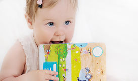 Portrait of cute smart baby girl with book in hands Royalty Free Stock Images