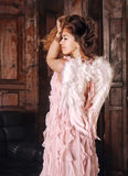 Portrait of a cute smiling angel woman posing in pink dress with wings. Stock Photography
