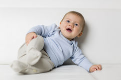 Portrait of cute smiling baby boy lying on sofa. Royalty Free Stock Image
