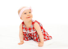 Portrait cute smiling baby in dress with headband crawls Royalty Free Stock Image