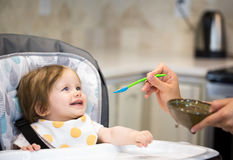 Portrait of cute smiling baby girl sitting in a highchair. And eating. Kitchen room interior Royalty Free Stock Photo