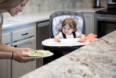 Portrait of cute smiling baby girl sitting in a highchair. And looking on freshly prepared pizza Royalty Free Stock Image