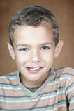 Portrait of a cute smiling boy. Closeup portrait of a 5 year old boy looking at the camera with beautiful eyes and smiling Stock Image