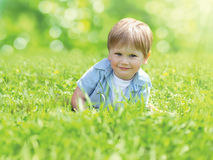 Portrait cute smiling child lying on grass in sunny summer day royalty free stock photos