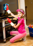 Portrait of cute smiling girl cleaning TV screen Stock Image