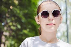 Portrait of cute smiling girl in the forest in sunglasses close up.  royalty free stock image