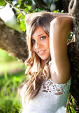 Portrait of cute smiling girl leaning to big tree Stock Photography