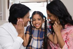 Portrait of cute smiling girl with mother and grandmother. At home Stock Image