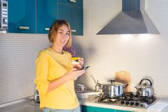 Portrait of cute smiling woman with phone hands and a mug of tea standing in the kitchen royalty free stock photo