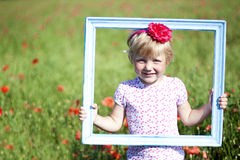Portrait of cute smiling girl with  in poppy field Stock Photos