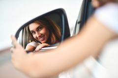 Portrait of cute smiling girl sit in the car and look at the car mirror. Portrait of cute smiling girl sit in the .car and look at the car mirror royalty free stock photos
