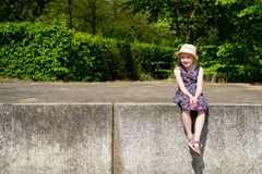 Portrait of cute smiling girl wearing hat sitting on retaining wall. On a beautiful summer day royalty free stock photo