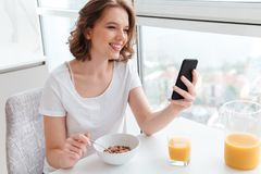 Portrait of cute smiling girl in white tshirt chatting on smartp. Hone while sitting and eating cornflakes at the kitchen table royalty free stock images