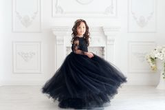 Portrait of cute smiling little girl in black princess fluffy dress stock photos