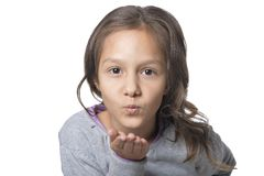 Portrait of cute smiling little girl blowing air kiss on white background stock photo