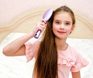 Portrait of cute smiling little girl child brushing her hair. Closeup stock images