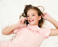 Portrait of cute smiling  little girl child calling by cell phone smartphone lying on the bed. At home royalty free stock photography