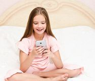 Portrait of cute smiling  little girl child playing with cell phone smartphone. Sitting no the bed at home stock photos