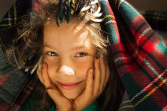 Portrait of cute smiling school girl look out from plaid Royalty Free Stock Image