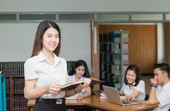 Portrait of cute smiling student reading book Stock Photo