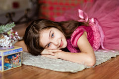 Portrait of a cute smiling young girl in a pink dress lying on t stock photo