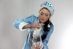 Portrait of cute snow maiden blowing soap bubbles Stock Image