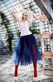 Portrait of cute strange freak girl. Attractive weird woman wearing motley corset, tights and tutu skirt in ruined place. Odd fash Stock Photo