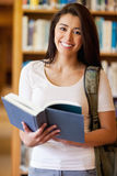 Portrait of a cute student holding a book. In the library Stock Photography