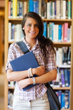 Portrait of a cute student posing with a book. In the library Stock Image