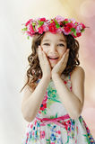 Portrait of cute surprised little girl in nice spring dress, with flower wreath on head, showing emotions. Portrait of cute surprised little girl in nice spring stock photo