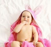 Portrait of cute sweet baby in towel lying on the bed at home Stock Photography