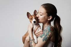 Portrait of a cute tattooed young woman hugging and kissing her little puppy basenji dog. Love between dog and owner. Isolated over white background royalty free stock images