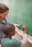 Portrait of a cute teacher and a pupil making an addition. On a blackboard Stock Photos