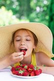 Portrait of Cute teen girl in big hat is eating strawberry at summer day royalty free stock photos