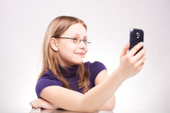 Portrait of a cute teen girl with phone taking selfie Royalty Free Stock Image