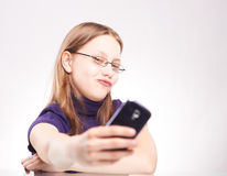 Portrait of a cute teen girl with phone taking selfie. Studio shot Royalty Free Stock Photography