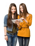 Teen girls sharing a tablet computer. Portrait of a cute teen girls sharing a tablet computer Royalty Free Stock Images