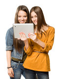 Teen girls sharing a tablet computer. Portrait of a cute teen girls sharing a tablet computer Royalty Free Stock Photography