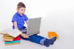Portrait of cute schoolboy sitting with books and typing on laptop keyboard. Portrait of cute teen schoolboy sitting near books and typing on laptop keyboard Stock Image
