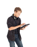 Portrait of a cute teenage boy with headphones and tablet computer. Stock Image