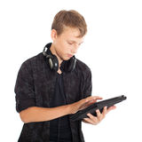 Portrait of a cute teenage boy with headphones and tablet computer. Royalty Free Stock Photos