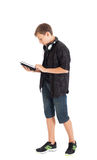 Portrait of a cute teenage boy with headphones and tablet computer. Royalty Free Stock Images