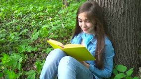 Portrait of cute teenage girl reading book and turning page leaning against tree trunk in forest in spring, studying. Cute teenage girl reading book and turning stock video