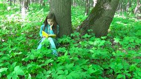 Portrait of cute teenage girl reading book and turning page leaning against tree trunk in forest in spring, studying. Cute teenage girl reading book and turning stock video footage