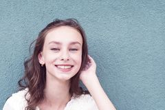 Pretty young girl with charming smile. Portrait of cute teenager with beautiful appearance posing outside. Happy cheerful female looking at camera with gladness royalty free stock image