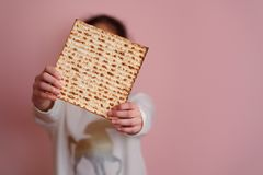Young girl holding matzah or matza. Jewish holidays Passover invitation or greeting card.Selective focus.Copy space. stock photography