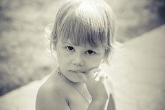 Portrait of cute thinking Caucasian blond baby gir Stock Image