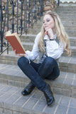 Portrait of Cute Thinking and Tranquil Caucasian Blond Female With Book Sitting Straight on Stairs Outdoors and Reading. Royalty Free Stock Photography