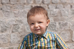 Portrait of a cute toddler against the stone wall Stock Image